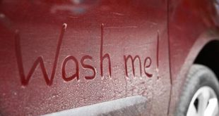 Written text WASH ME on dirty car